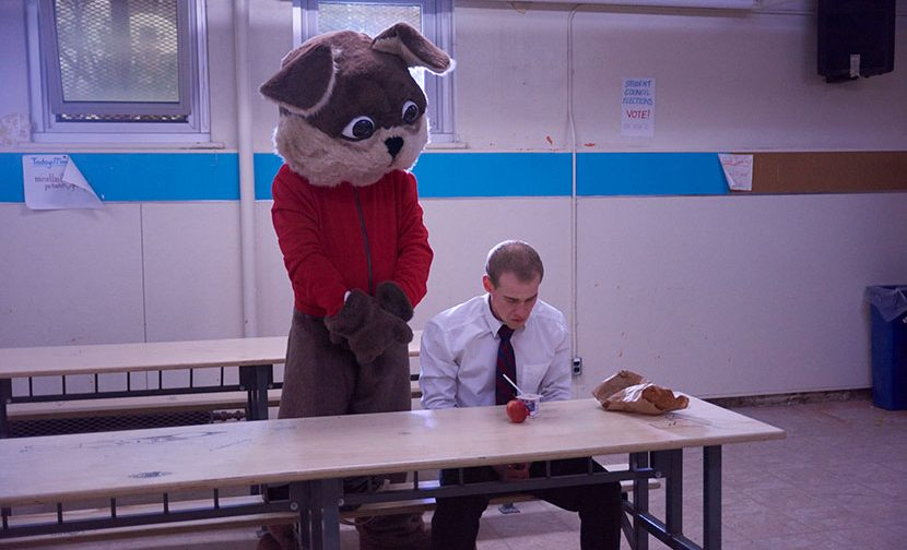 The Brantwood mascot and a male student in the cafeteria.