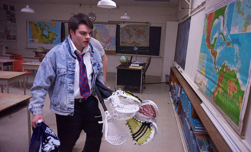Brantwood male athlete carries lacrosse equipment.