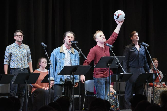 Two male performers one has a soccer ball
